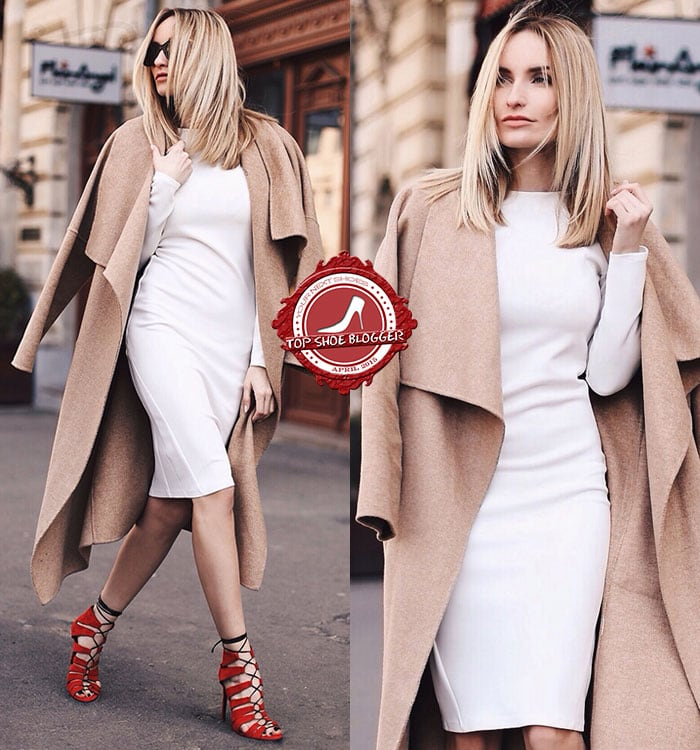 Silvia wears a white dress with a tan coat