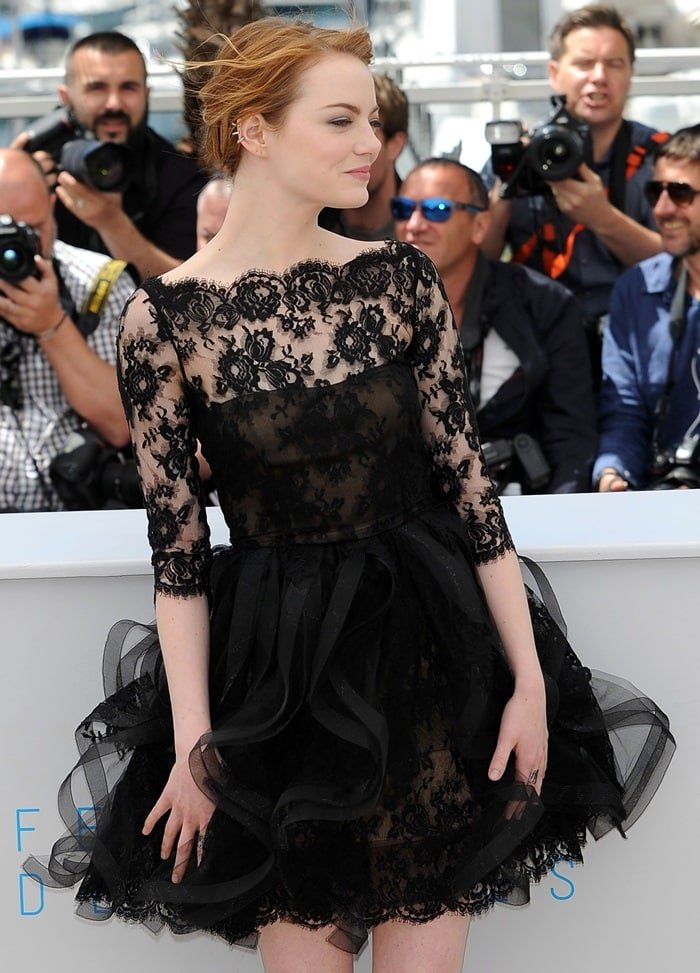 Emma Stone ina cocktail dress with frilly organza ruffles and a lace scalloped neckline