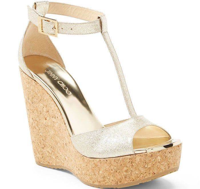 Embossed goldtone hardware adorns the toe of a fierce T-strap sandal elevated on a towering cork wedge.