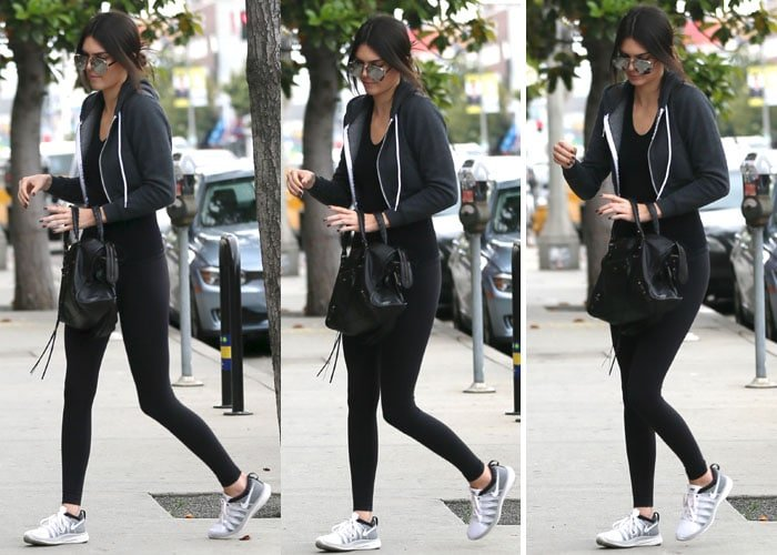 Kendall Jenner looked like she had just been working out in a pair of black tights and a tank top from American Apparel, which she wore under a black zip up hooded jacket