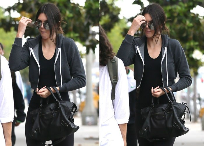 Kendall Jenner wearing a black zip up hooded jacket