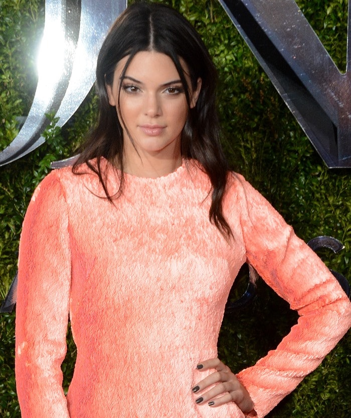 Kendall Jennerin a custom peach mini dress from Calvin Klein featuring layered sequins, a high neckline and long sleeves