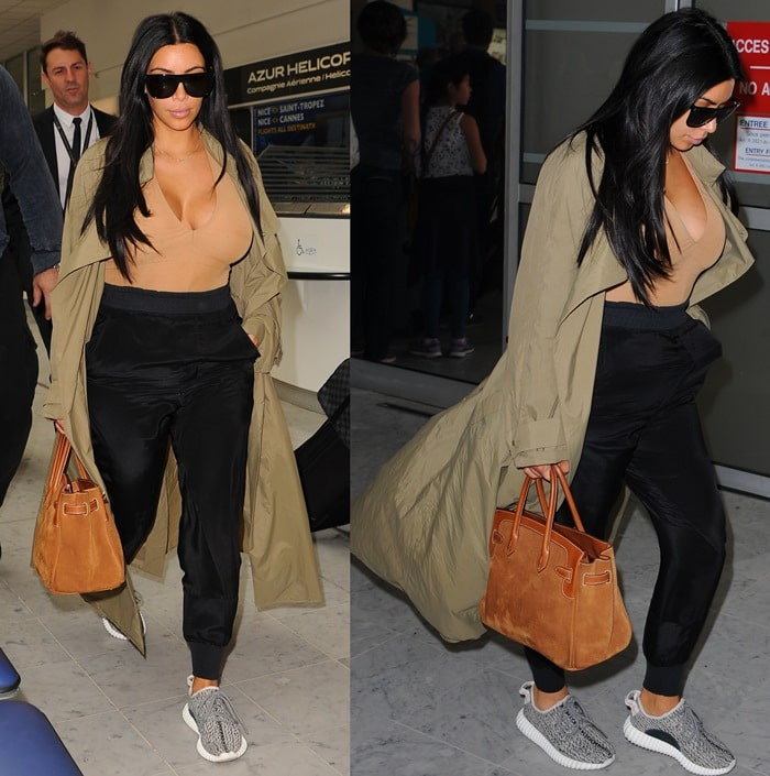 """Kim wore neutral tones for her airport stroll, opting Haider Ackermann jogging bottoms, a suede Hermes bag, an olive duster jacket and a pair of """"Yeezy 350 Boost"""" sneakers"""