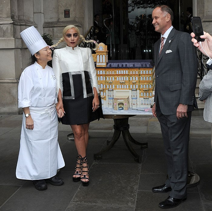 Lady Gaga posing with a very detailed custom cake in celebration of the 150th anniversary of London's first grand hotel