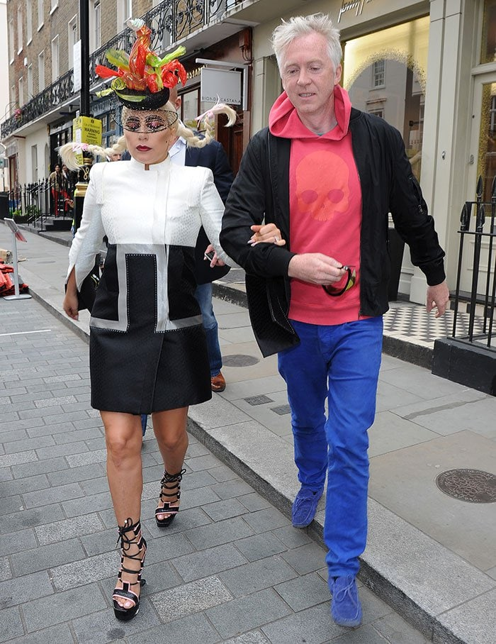 Lady Gaga wearing a lobster-inspired hat while arm in arm with Philip Treacy as they leave his shop in Belgravia, London, on June 10, 2015