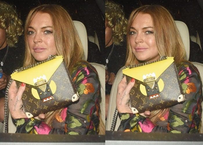 Lindsay Lohan shows off her Louis Vuitton purse