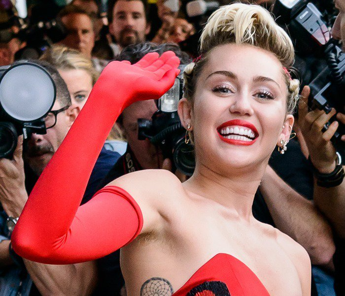 Miley Cyrus smiles in red, showing off her underarm hair and ribcage tattoo