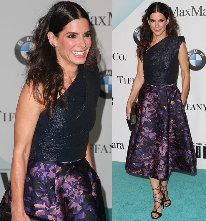 Sandra Bullock lets her brown hair fall around her shoulders in curls as she poses for photos