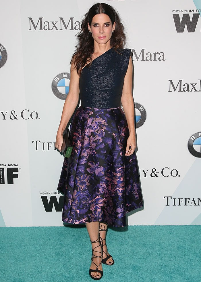 Sandra Bullock poses in front of a photo backdrop in a Monique Lhuillier ensemble