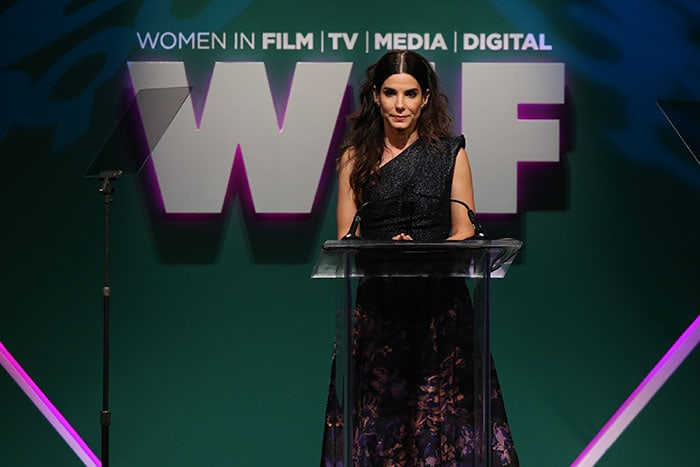 Sandra Bullock stands at a podium at the Women in Film 2015 Crystal + Lucy Awards