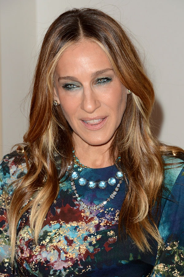 Sarah Jessica Parker wearing layered jewel necklaces and shimmery blue eye makeup that matches her blue patterned dress