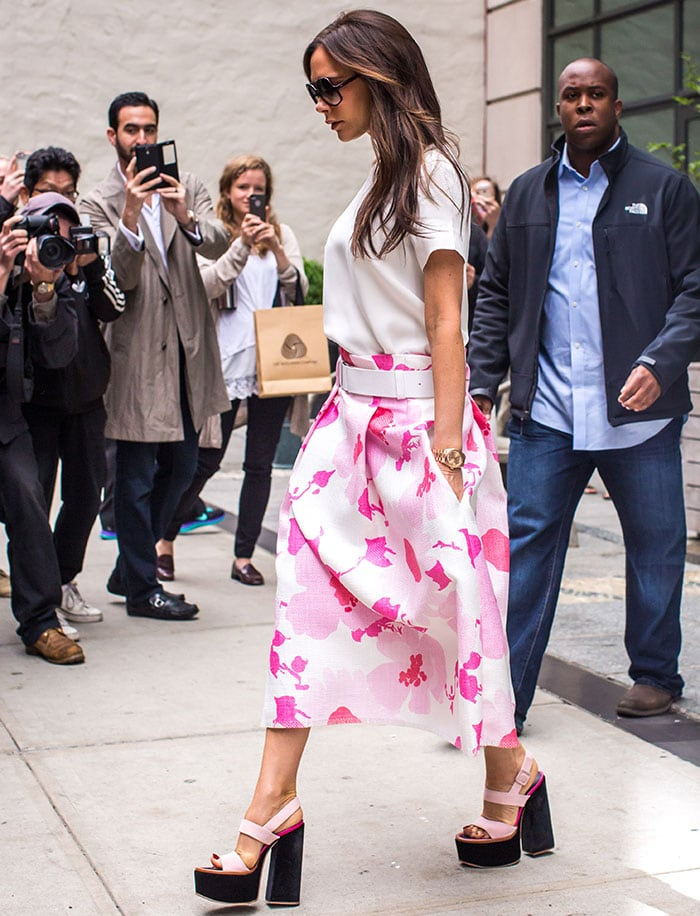 Victoria Beckham flashed her legs in a pink floral raffia midi skirt with interesting belt detail