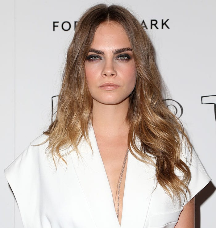 Cara Delevingne let her center-parted curled tresses fall loosely on her shoulders