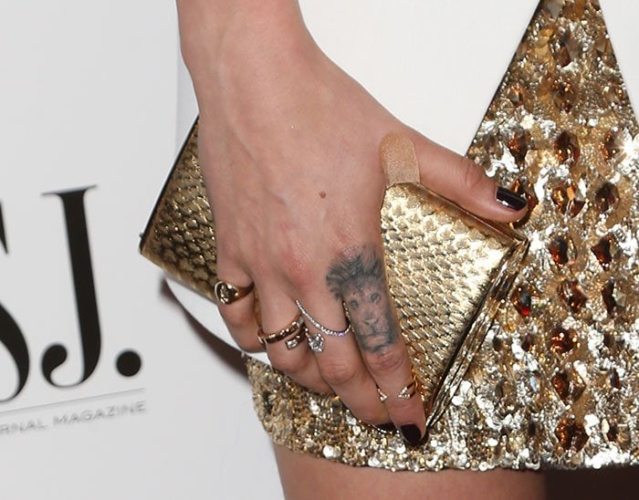 Cara Delevingne carrying a gold clutch and wearing a few rings