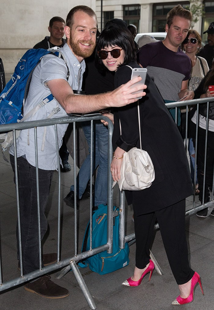 Carly Rae Jepsen takes a photo with a fan outside the BBC Radio 1 studios in London