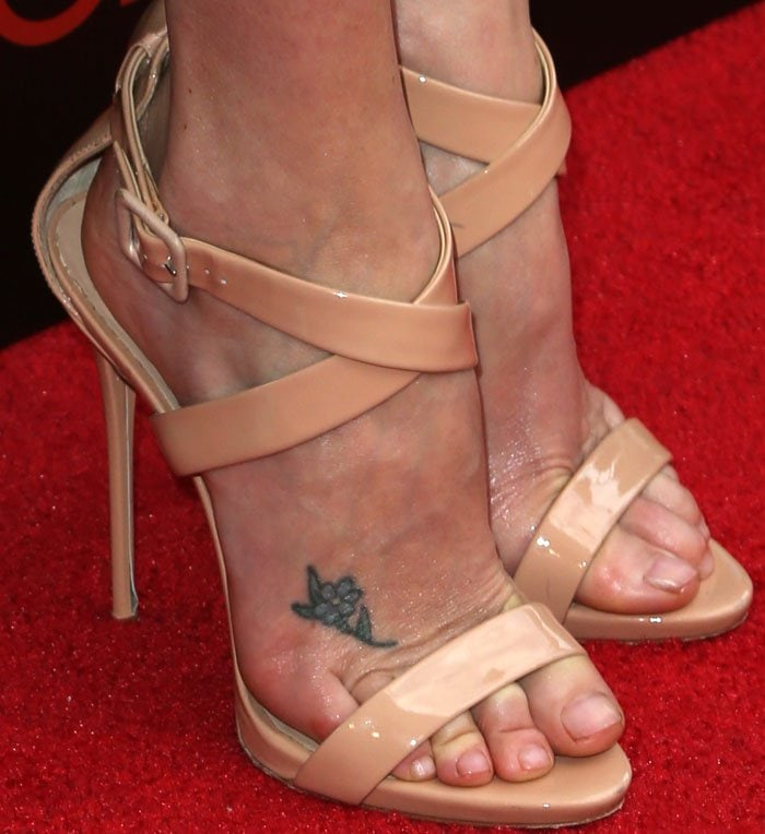 Charlize Theron has a small blue flower tattooed on the top her right foot