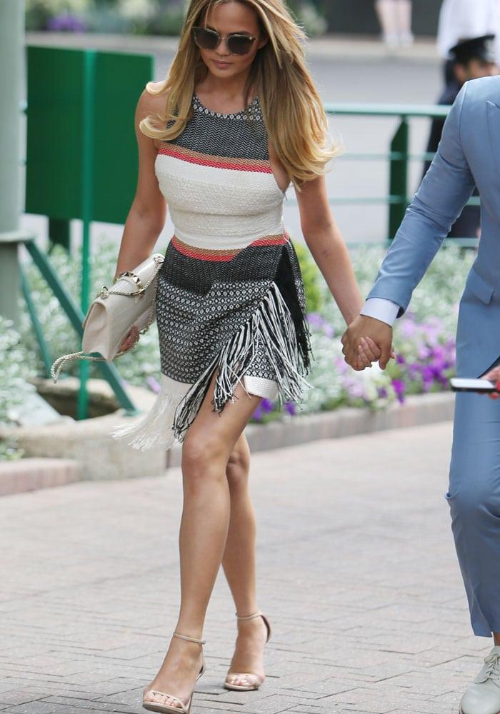 Chrissy Teigen flaunts her toned legs in a Magda Butrym dress