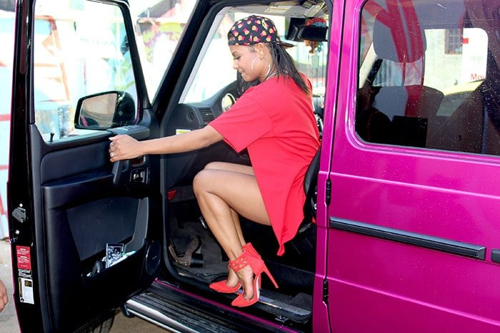 Christina steps into a fuchsia vehicle in her all-red look
