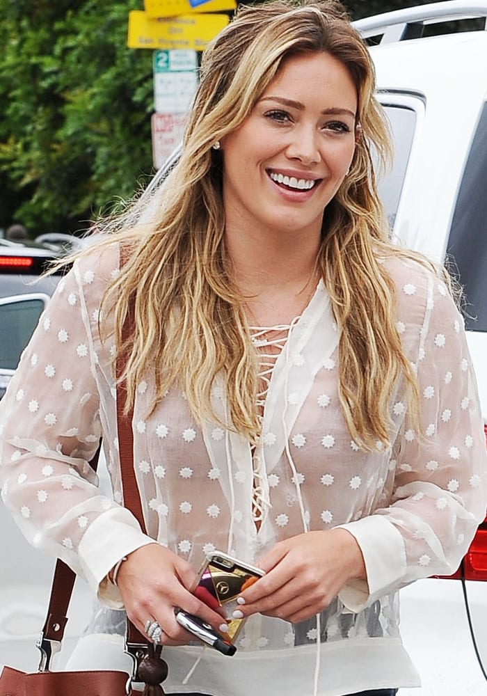 Hilary Duff flashes her pretty teeth in a white sheer top
