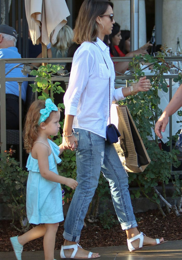 Jessica Alba looks casual and chic in flat white sandals, jeans and a simple white button-up