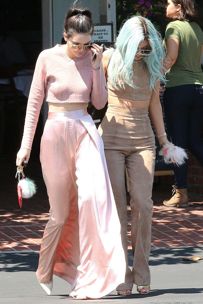 Kendall and Kylie looking down at the ground to avoid the cameras