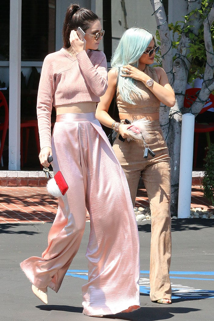 Kendall and Kylie touching their hair at the same time to partially hide their faces from the paparazzi