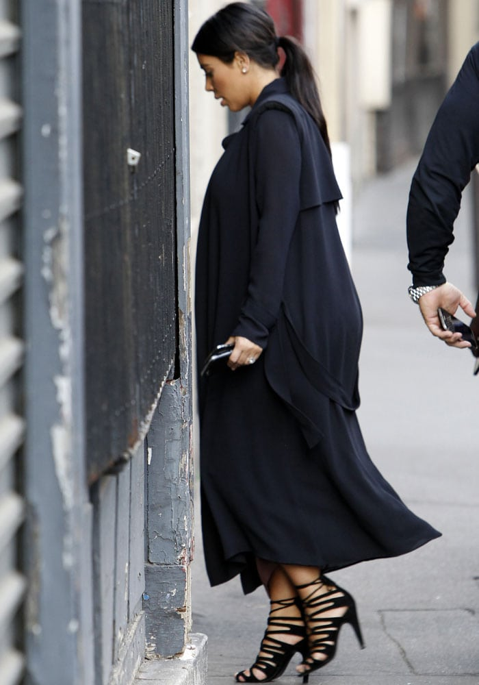 Kim Kardashian stepped out in a figure-hugging color block dress, which she paired with a flowy trenchcoat and her favorite Hermès Impulsion heels in black