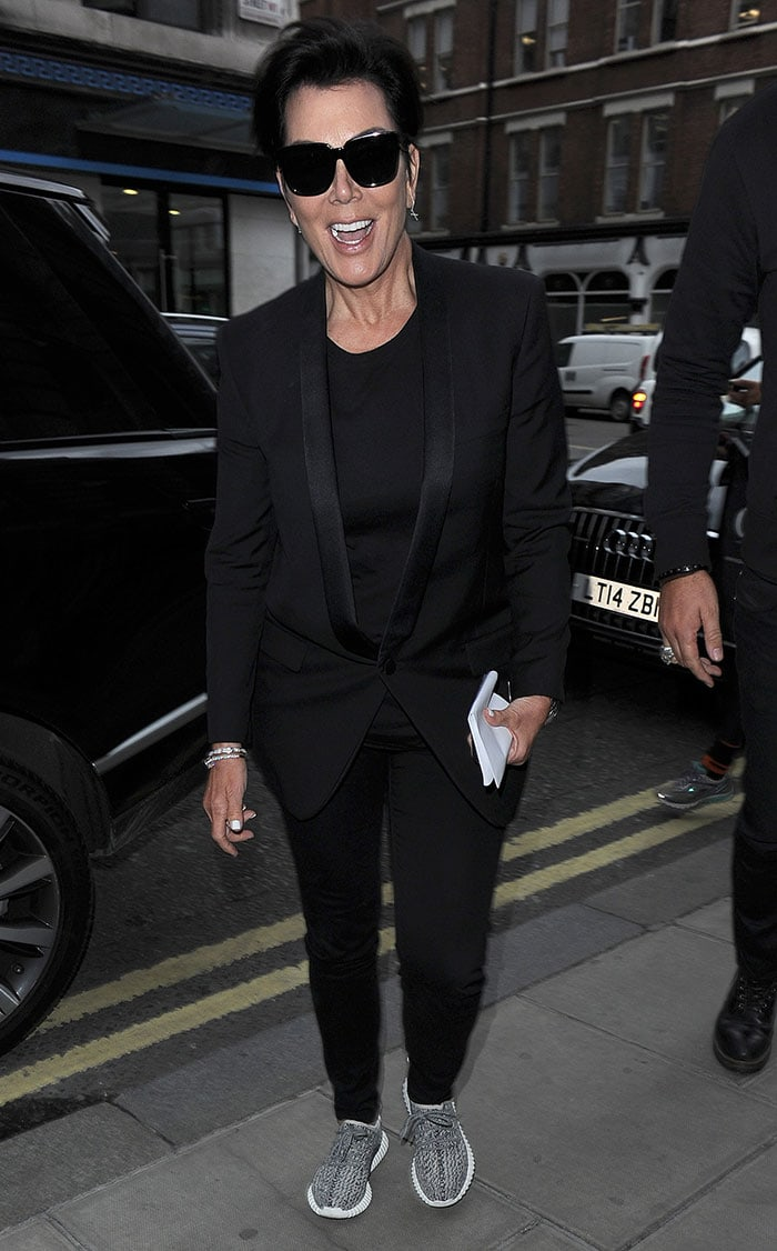 Kris Jenner rocks an all-black look comprised of slim-fit pants, a tuxedo blazer and a pair of Yeezy Boost 350 sneakers