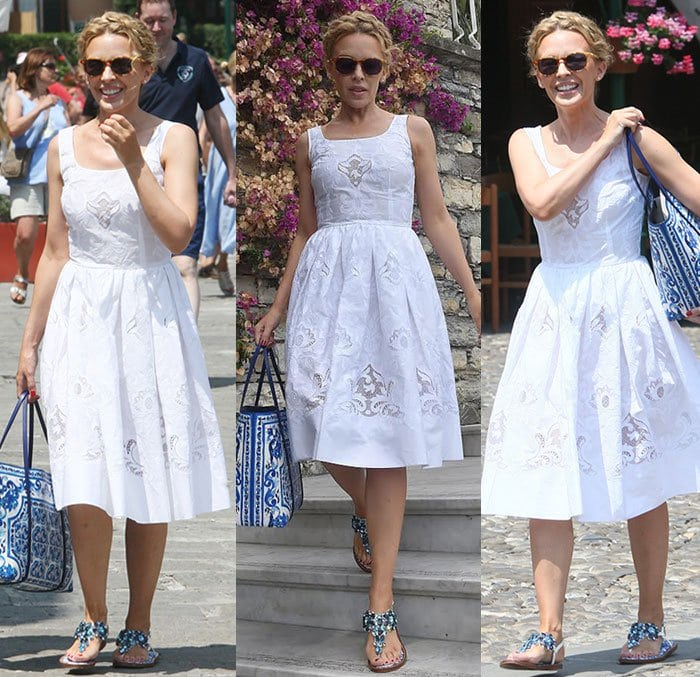 Kylie Minogue is all smiles as she enjoys her holiday in a blue-and-white summery look, complemented by a braided updo and dark sunglasses