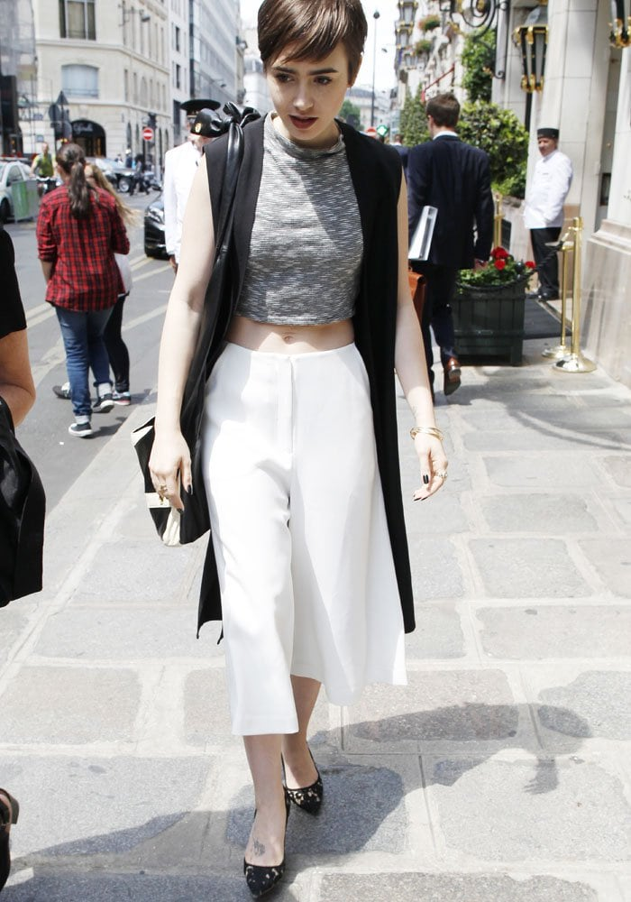 Lily Collins wears a full-length Topshop sleeveless duster in Paris