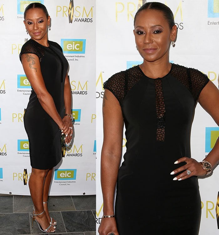Mel B. shows off her shoulder tattoo as she poses in front of a branded backdrop