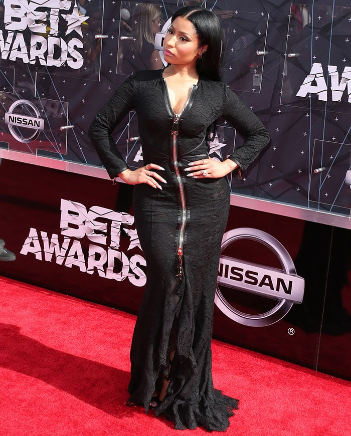 Nicki Minaj slipped into a $9,200 figure-hugging Givenchy gown in black floral lace featuring long sleeves with zipper trims, a flared ruffled skirt, and a huge zip fastening along the front