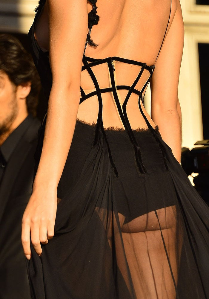 Rosie Huntington-Whiteley put on a cheeky display in a sheer black Versace creation that showed off her taut model body