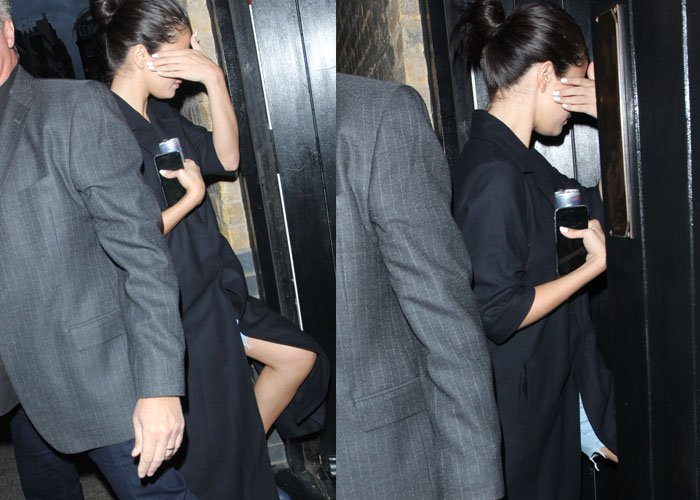 Selena Gomez hides her face with a white-manicured hand as she arrives for a birthday dinner in London