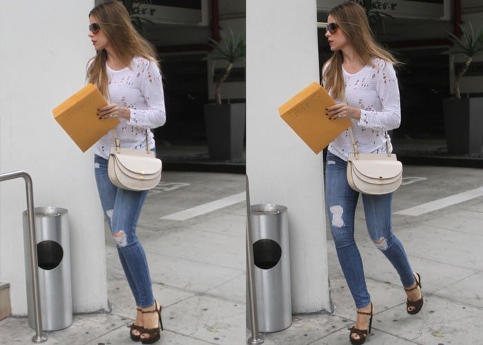 Sofia Vergara holds an envelope as she struts through town in platform heels