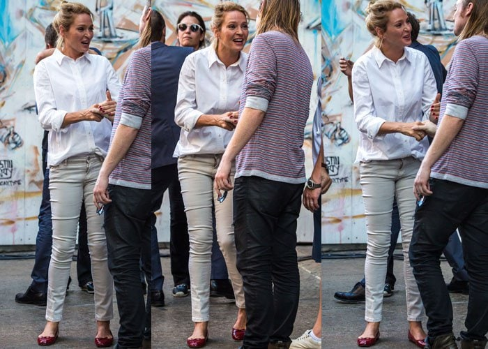 """Uma Thurman smiles on the set of her new project """"The Brits are Coming"""" in an all-neutral outfit paired with red flats"""