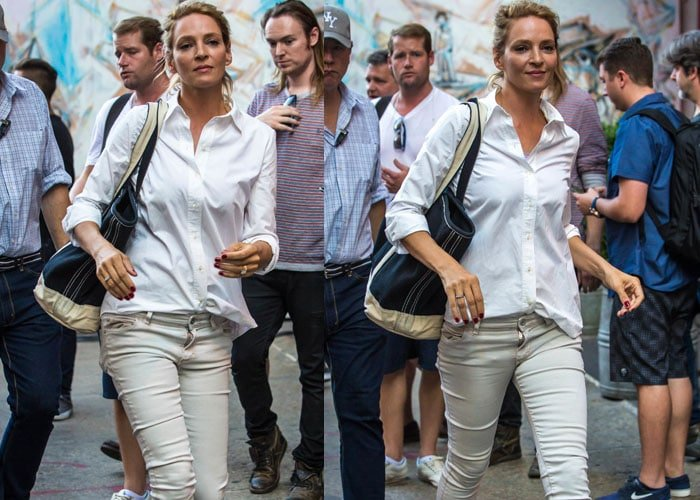 Uma Thurman carries a large navy tote bag with her all-neutral outfit, comprised of unbelted pants and a hastily-tucked button-up