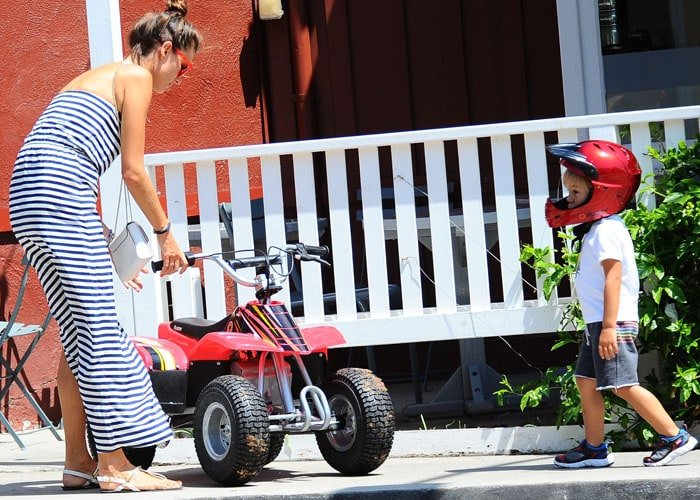 Alessandra Ambrosio wears her brown hair up in a topknot as she plays with her son Noah