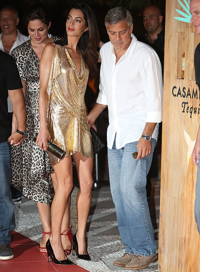 Amal Alamuddin-Clooney taking her place alongside husband George to pose next to a wodden display case of Casamigos tequila