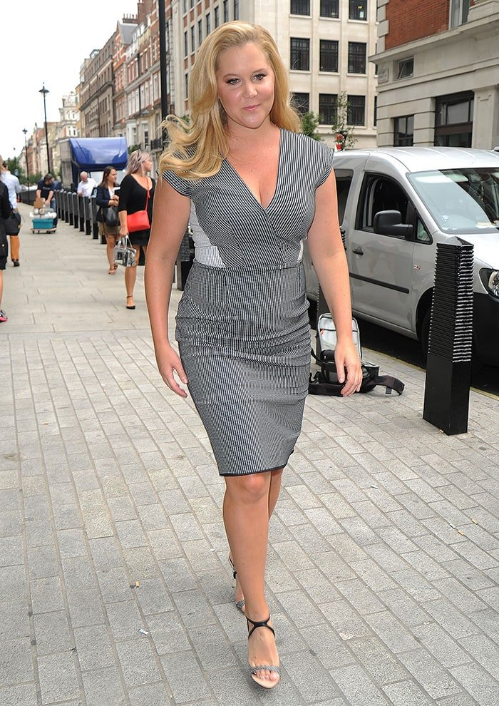 Amy Schumer'sdress features a cleavage-baring V-neck and a zipper fastening and a slit detail at the back