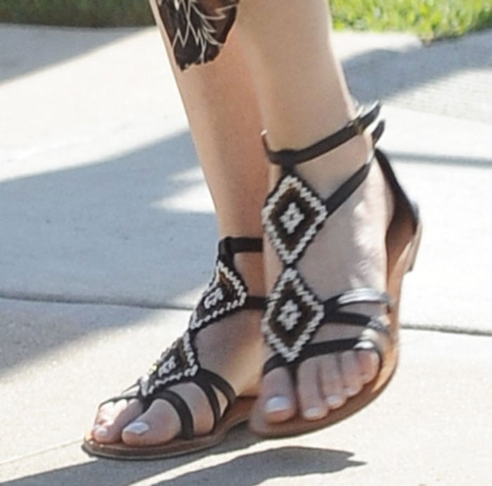 Charlize Theron shows off perfectly pedicured toenails in a pair of Aztec-beaded sandals