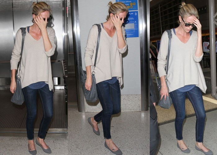 Charlize Theron completed her airport fashion with sunglasses, a gray tote, and gray suede ballerina flats