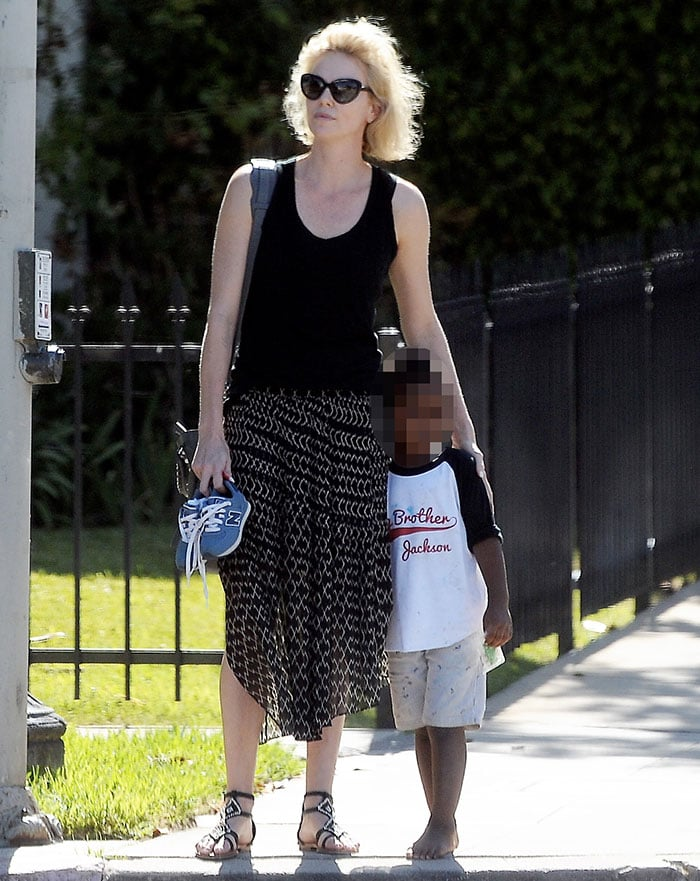 Charlize Theron holds her son Jackson's shoes as the two pause on a sidewalk