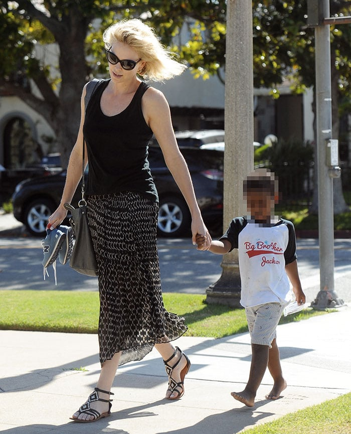 Charlize Theron's blonde bob blows in the wind as she takes a stroll with her barefoot son, Jackson