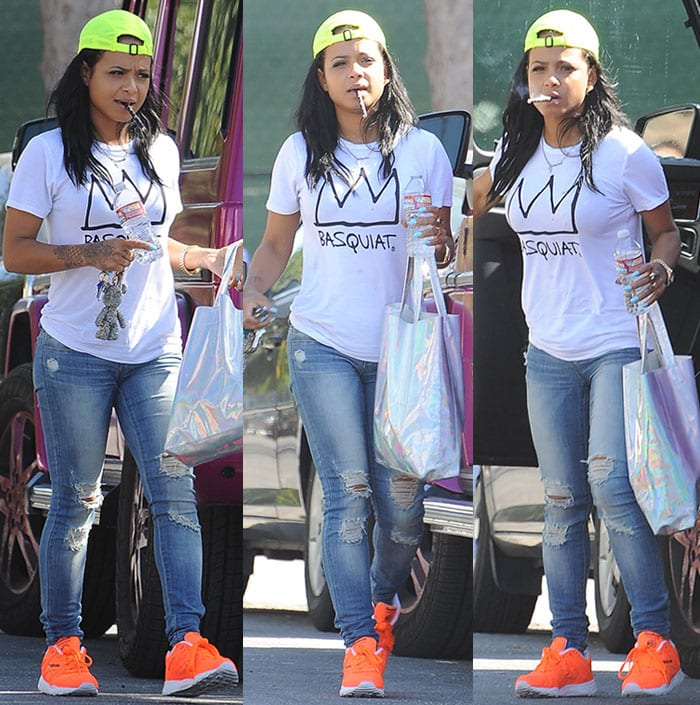Christina Milian pops a vape pen into her mouth as she sports a pair of bright orange Reebok sneakers