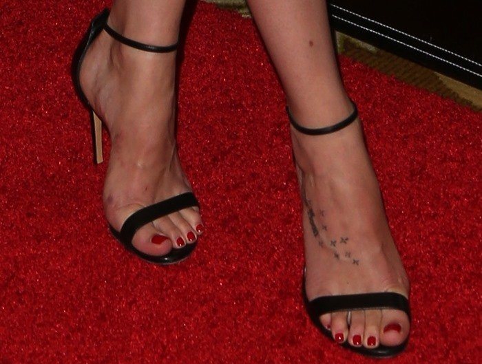 Dakota Johnson showed off her feet and foot tattoo in black sandals