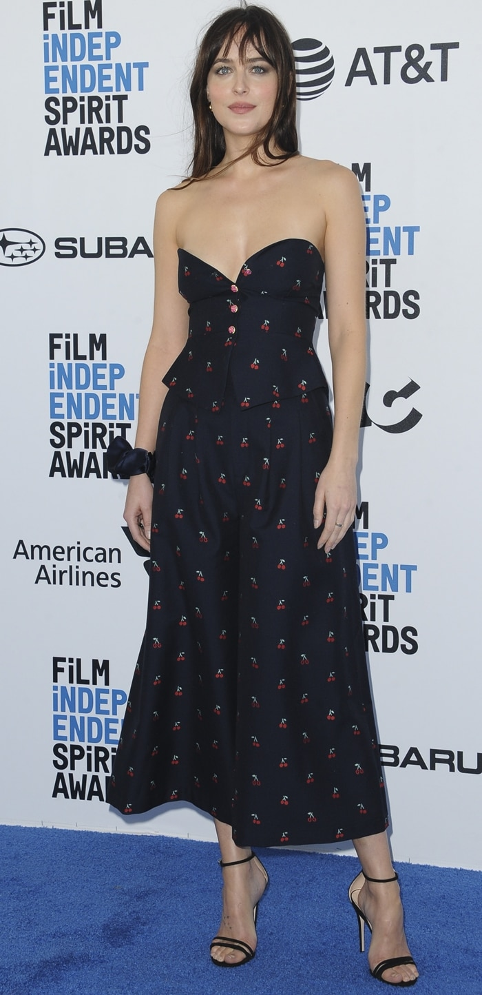 Dakota Johnson looked gorgeous in a cherry-printed jumpsuit on the blue carpet at the 2019 Film Independent Spirit Awards