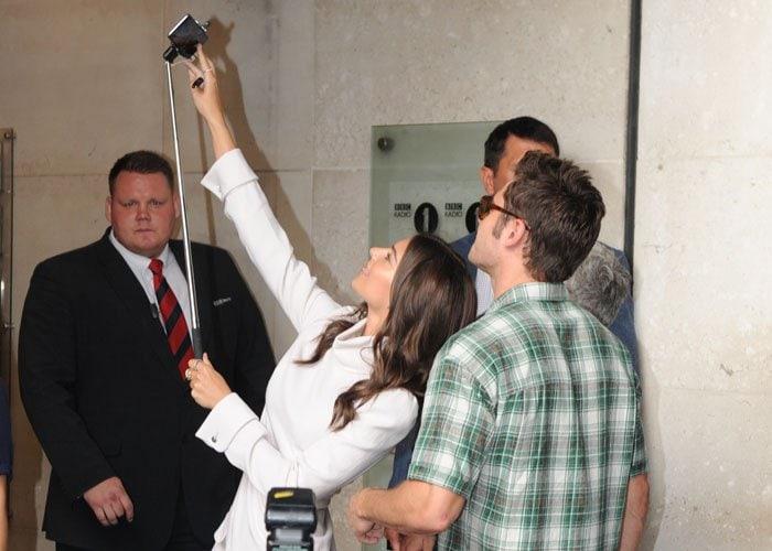 Emily Ratajkowski positions a selfie stick to take a photo with costar Zac Efron