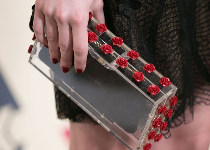 Emma Roberts clasps a rose-embellished Charlotte Olympia clutch with her manicured fingers
