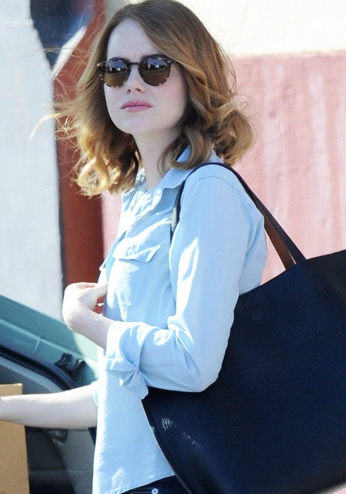 "Actress Emma Stone carries a black tote on the set of ""La La Land"""